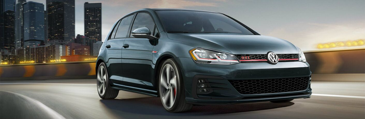 Exterior view of a dark green 2019 Volkswagen Golf GTI driving down a city highway