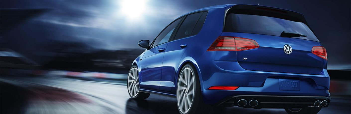 Exterior view of the rear of a blue 2019 Volkswagen Golf R driving around a wet race track