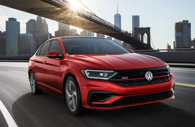 Exterior view of the front of a red 2019 Volkswagen Jetta GLI driving down a highway in the city
