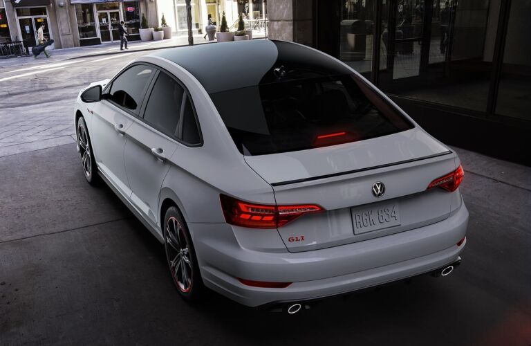 Exterior view of the rear of a white 2019 Volkswagen Jetta GLI parked in the city