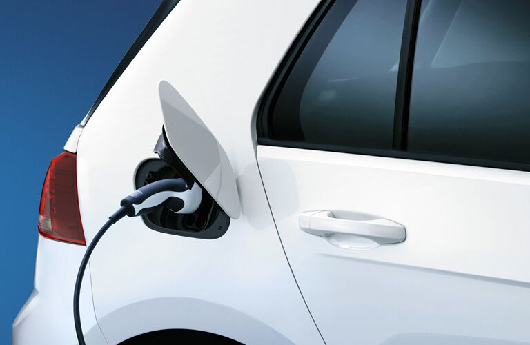 Exterior closeup view of the electric charging port with charger inserted on a white 2019 Volkswagen e-Golf