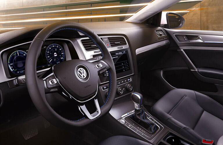 Interior view of the steering wheel and front seating area inside a 2019 Volkswagen e-Golf