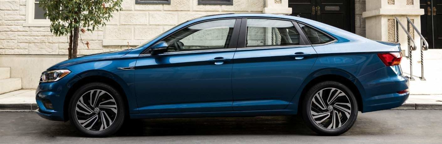 Side profile of the 2019 Volkswagen Jetta parked in front of a tree and sidewalk