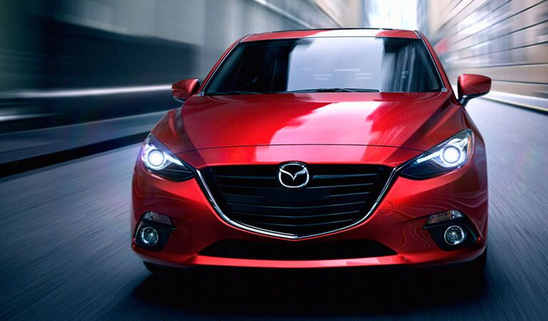 front view of a 2016 Mazda3 driving down an alley