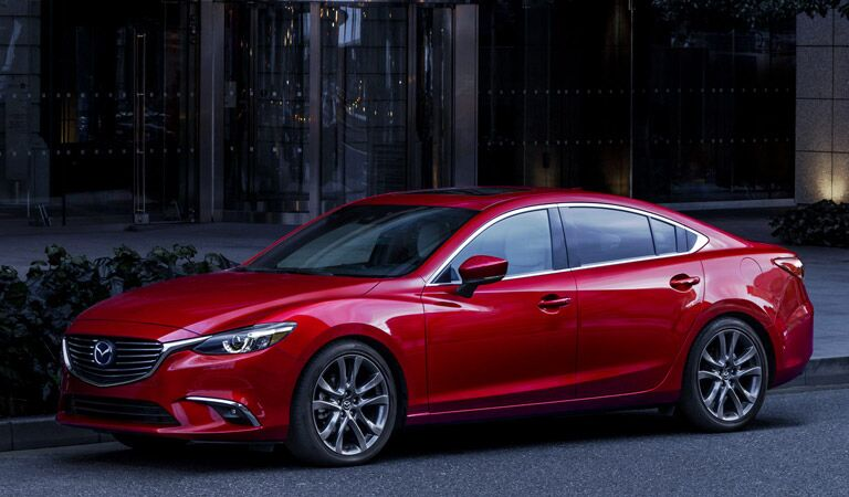 Red 2017 Mazda6 parked in front of a city building with a glass door