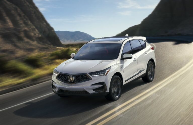 2019 Acura RDX in white driving on a road in the mountains