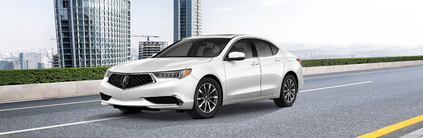 2019 Acura TLX in white driving on an empty city street