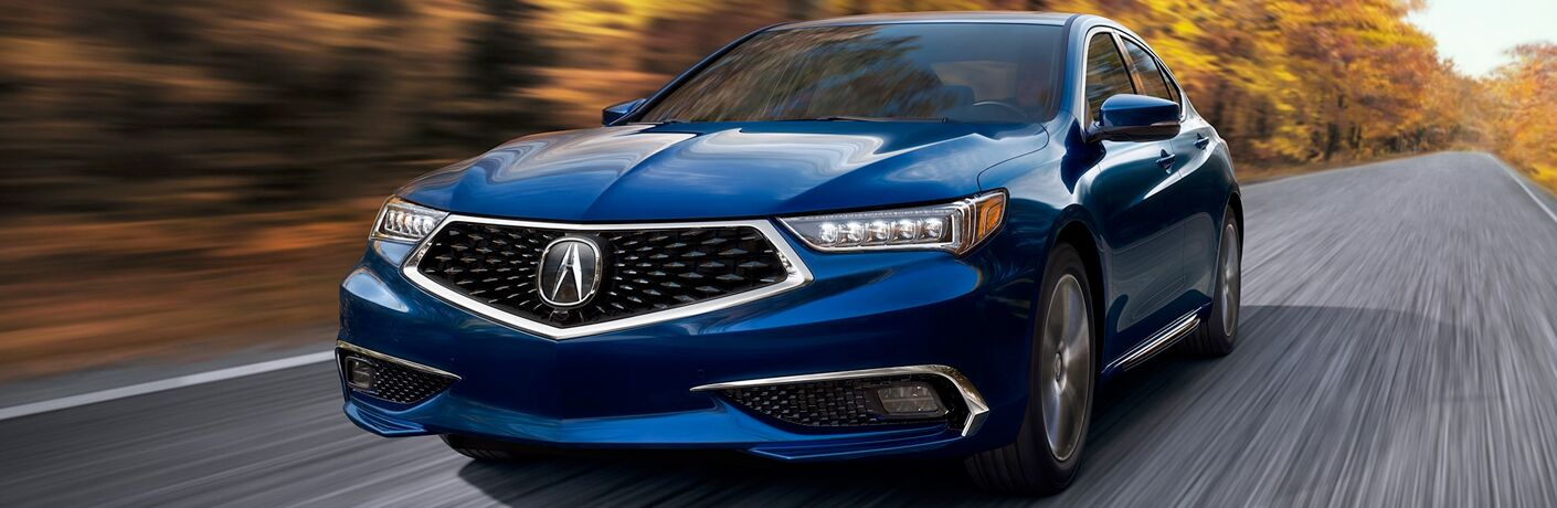 A front end photo of a blue 2018 Acura TLX in motion on the road.