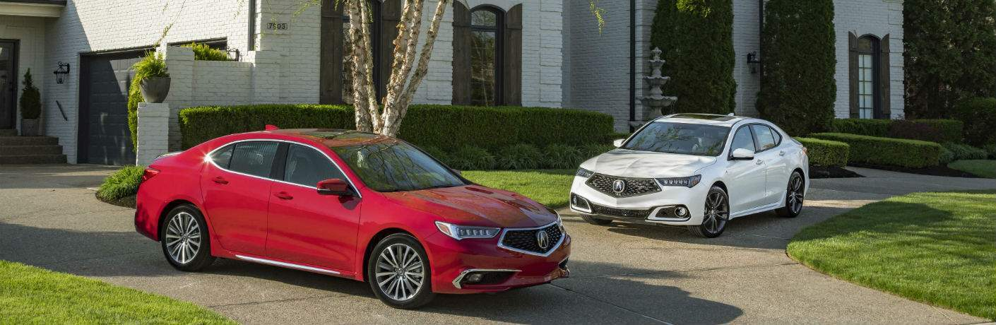 A red 2018 TLX and a white 2018 TLX parked in a driveway