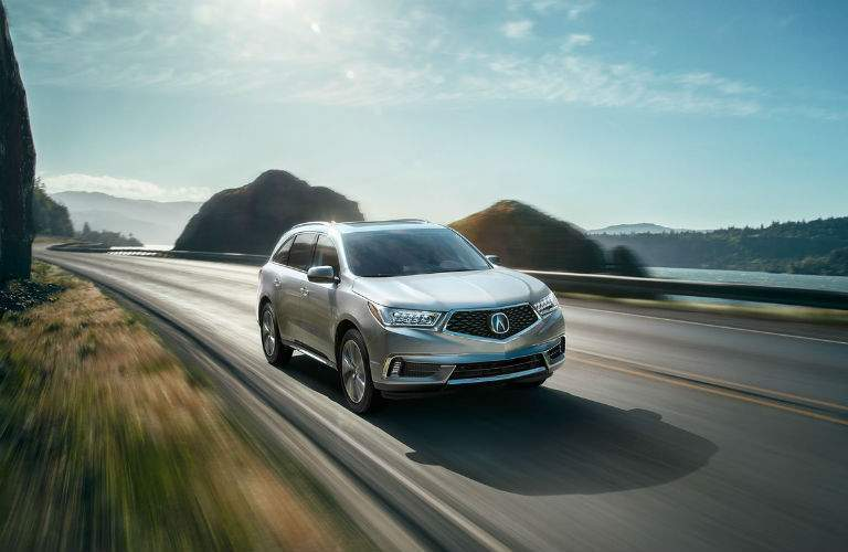 Photo of the 2018 Acura MDX Advance coming down the road past hills and a river