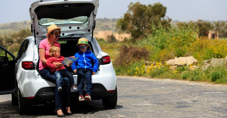 family looking at map resting in a compact crossover cargo area