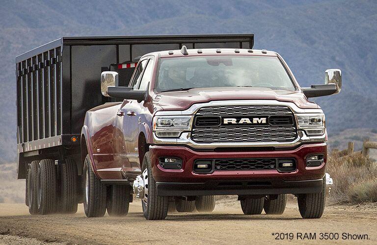 2020 Ram 3500 exterior shot pulling excavation trailer on dirt road