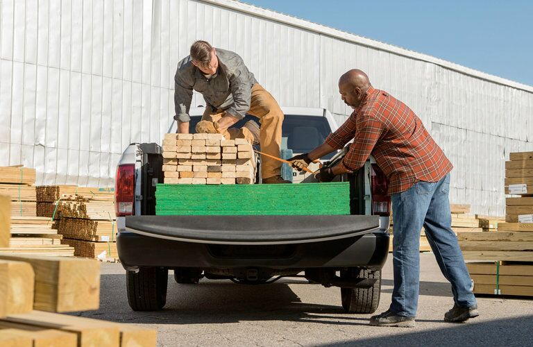 People loading wood into the 2018 Ram 1500
