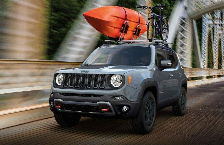 2018 Jeep Renegade driving on a bridge with gear on the top racks