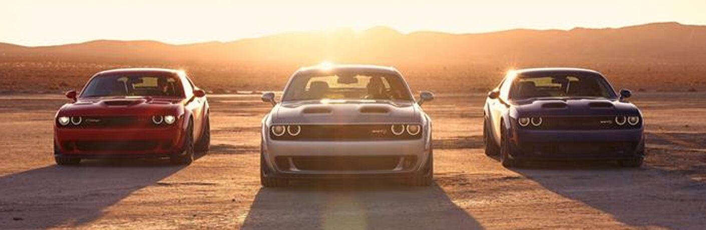 Three 2019 Dodge Challengers parked in a row in the desert