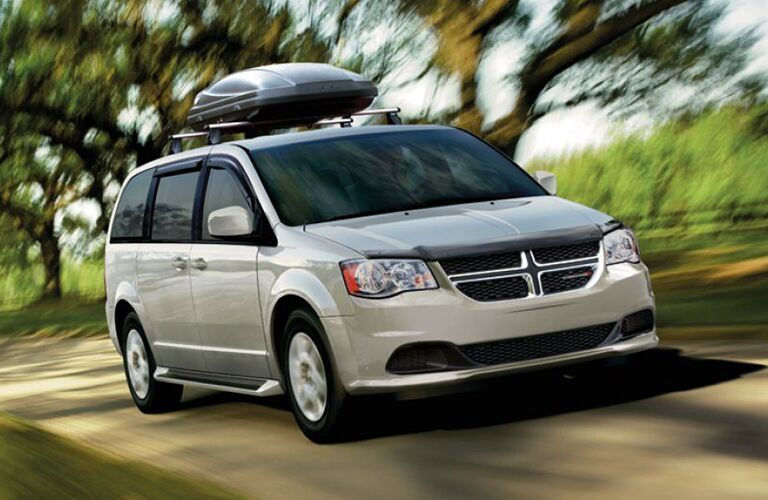 2019 Dodge Grand Caravan driving in the woods with gear attached to the roof rails