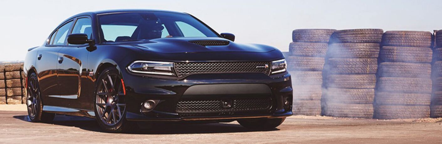 2019 Dodge Charger parked in front of a stack of tires