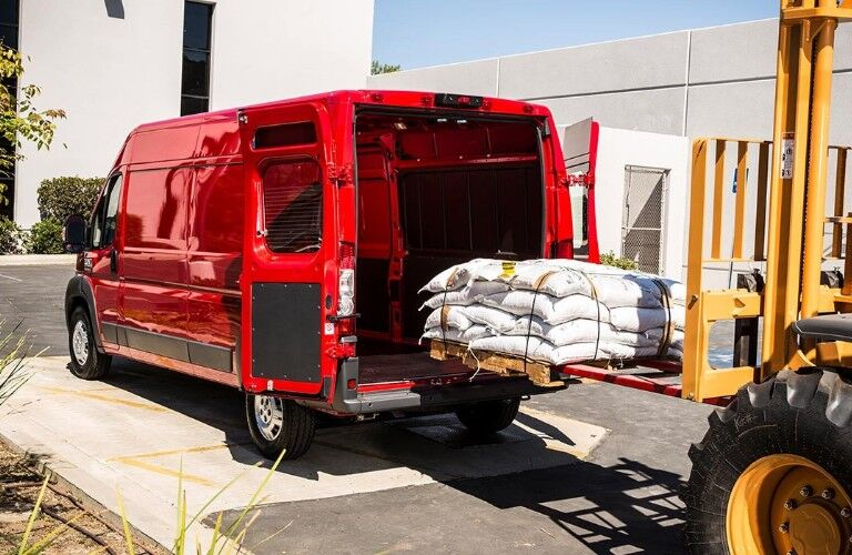 red 2019 Ram ProMaster Van being loaded from a fork lift
