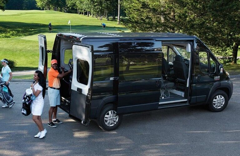 passengers coming out of a black 2019 Ram ProMaster Van