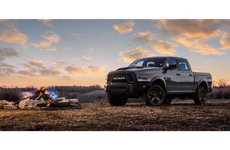 2019 Ram 1500 Classic dark paint in front of campfire with sunset clouds and sky