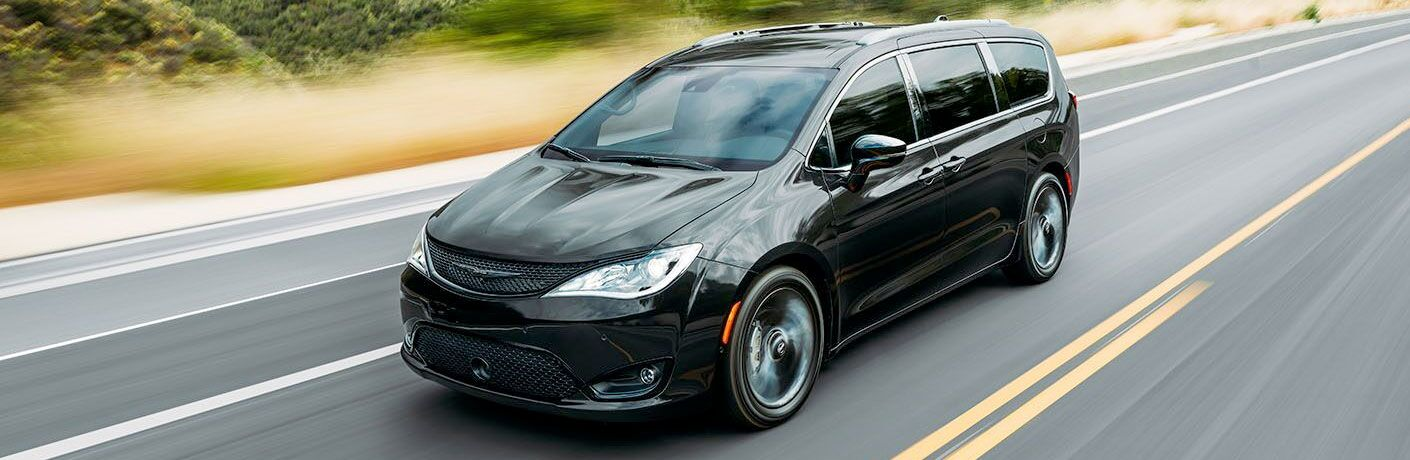 2020 Chrysler Pacifica driving on highway facing right black paint motion blur showing front bumper and driver side