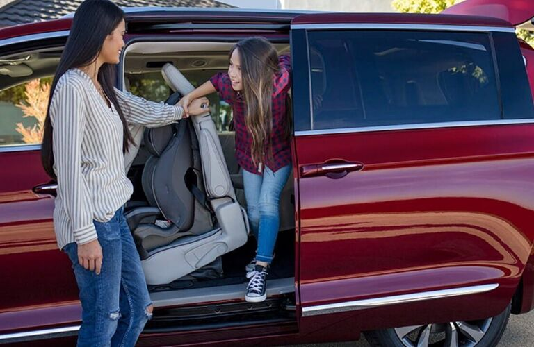 2020 Chrysler Pacifica red paint shot from driver side with open driver side sliding door child inside