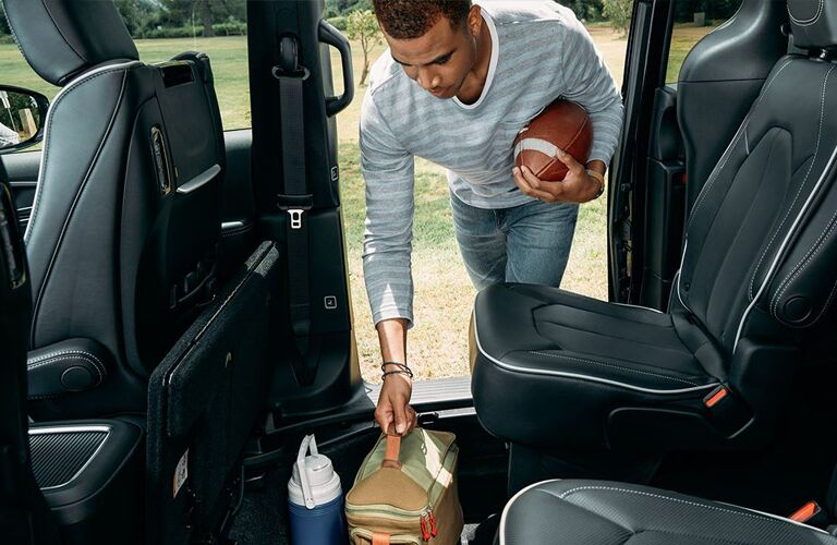 2020 Chrysler Pacifica interior shot showing man loading cargo and holding football