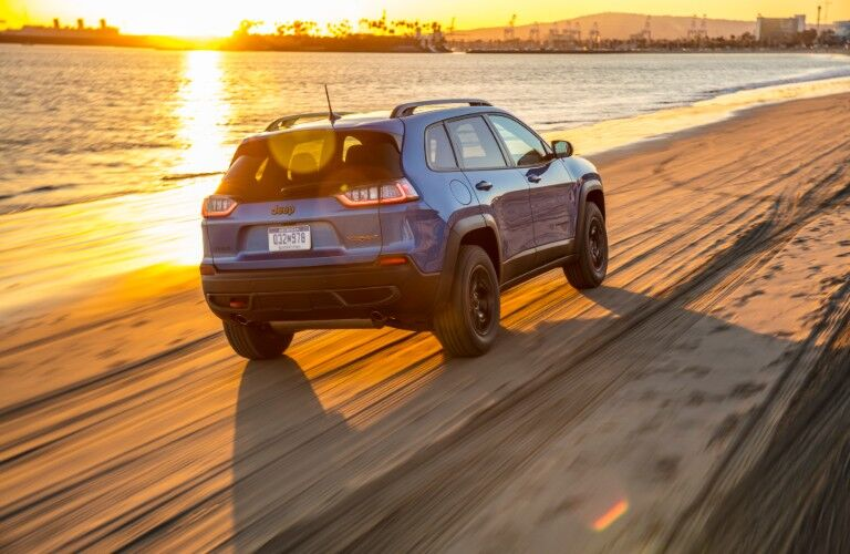 blue 2020 Jeep Cherokee driving into sunset on a beach