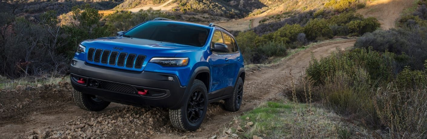 2020 Jeep Cherokee blue driving up gravel trail in mountains