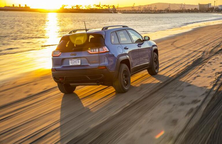 2020 Jeep Cherokee driving away from shot at sunset on beach