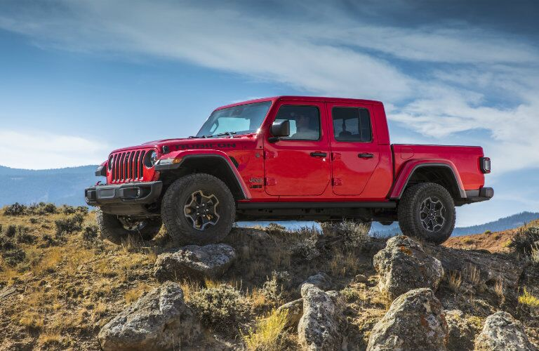 2020 Jeep Gladiator red parked on top of rocky surface with blue sky background