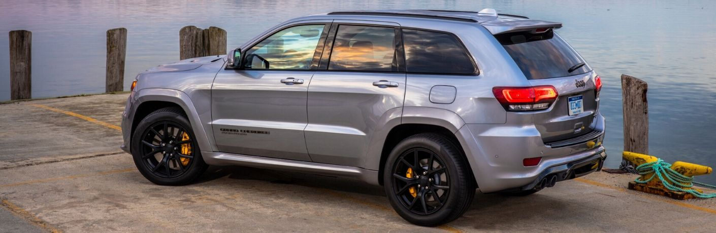 2020 Jeep Grand Cherokee light blue or grey parked on dock in front of water