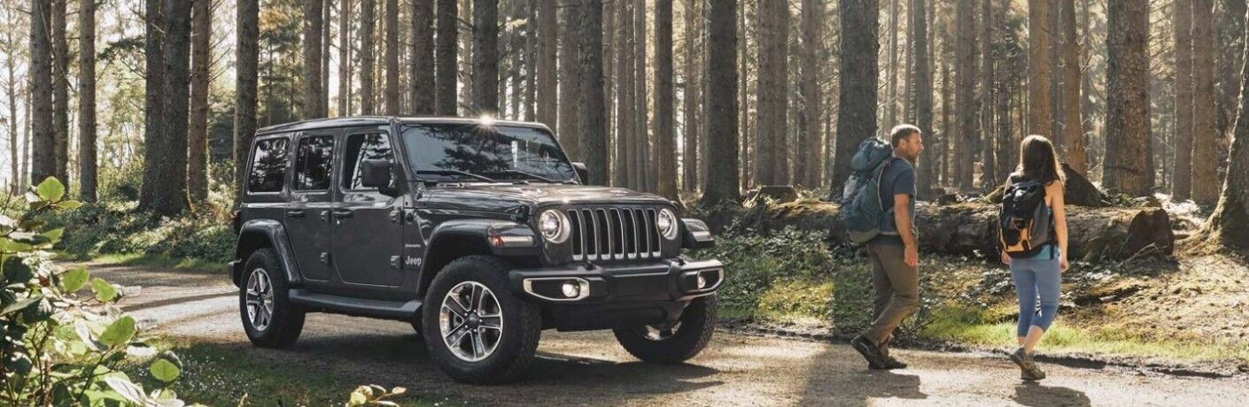 2020 Jeep Wrangler in woods with couple hiking