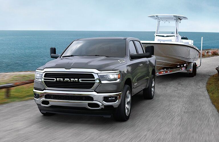 2020 Ram 1500 blue paint pulling boat in trailer on seaside road showing front bumper and driver side doors