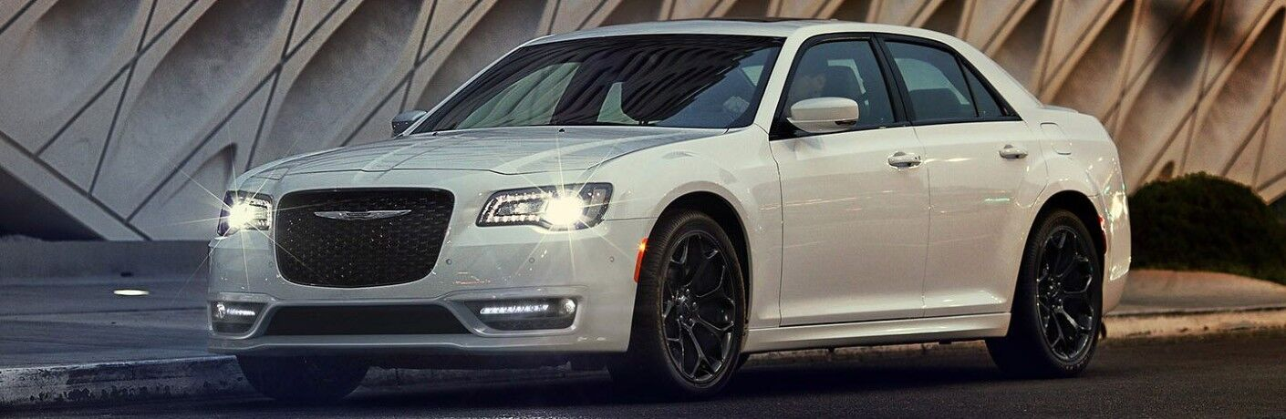 2020 Chrysler 300 white paint parked on side of city road with headlights on in front of stonework
