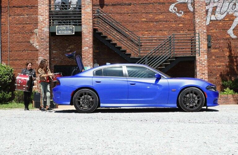 2020 Dodge Charger blue paint parked outside apartment building with drums being loaded into trunk