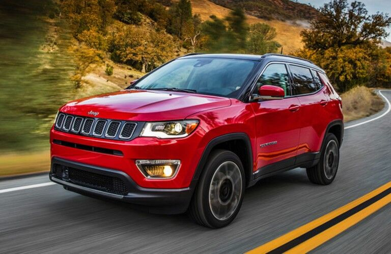 Red 2020 Jeep Compass driving on country road