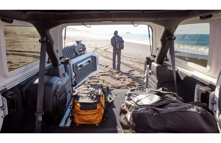 2020 Jeep Wrangler shot from inside wrangler back pointed out at man on beach