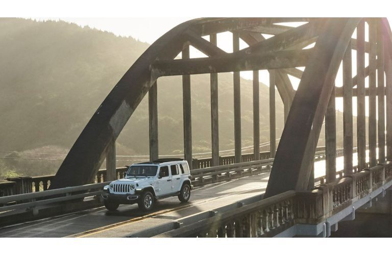 2020 Jeep Wrangler white driving over bridge distant shot