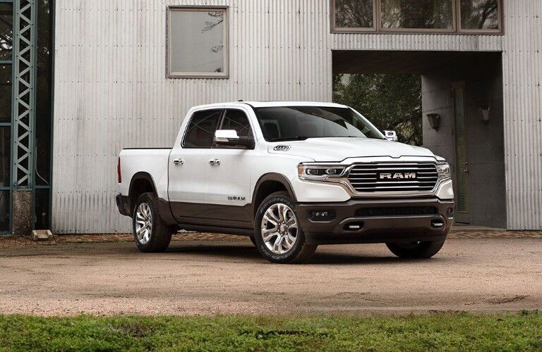 2020 Ram 1500 white painted linear grille parked in front of farm building or work site