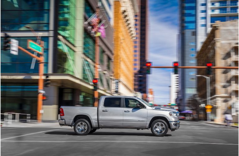 2020 RAM 1500 Big Horn White driving to the right on city street