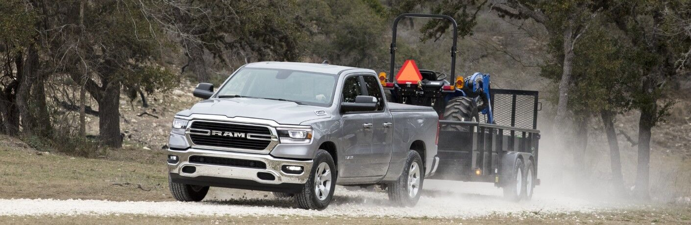 2020 RAM 1500 Big Horn exterior driving with trailer on dusty road