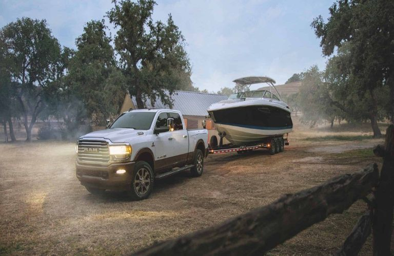 2020 Ram 2500 white towing boat dusty road