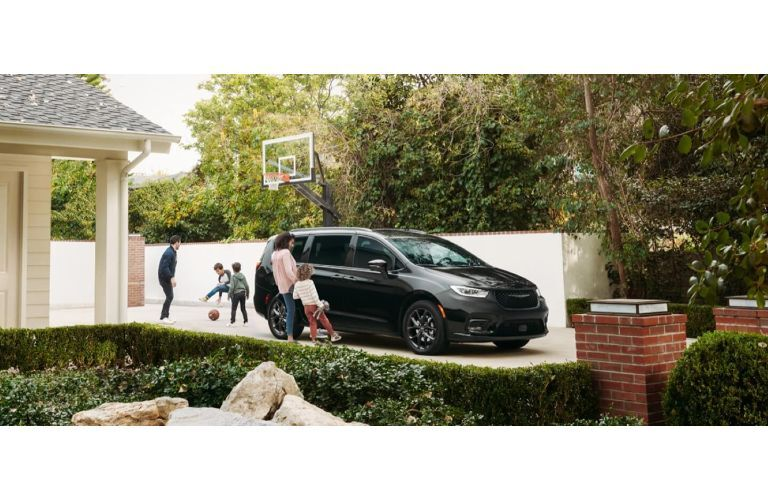 2021 Chrysler Pacifica parked in driveway with people playing basketball