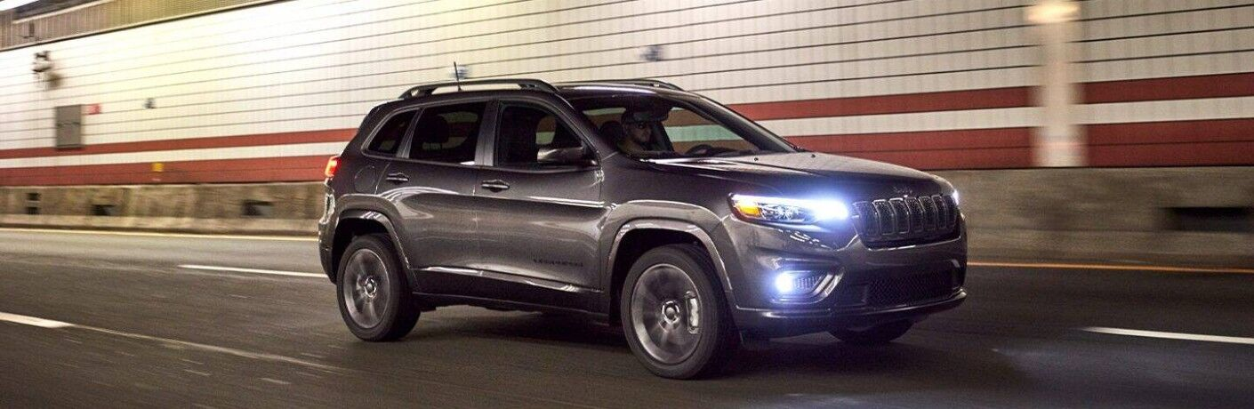 2021 Jeep Cherokee exterior grey driving in tunnel past white and red brick wall