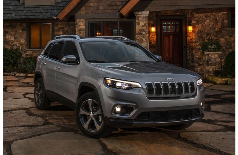 2021 Jeep Cherokee grey parked in front of stone house