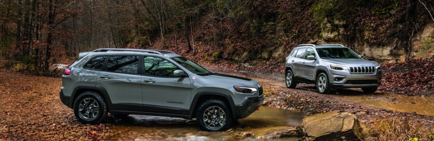 2021 Jeep Cherokee two models parked on brown leaves by stream