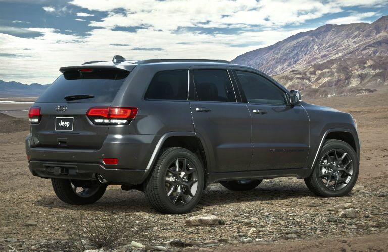 2021 Jeep Grand Cherokee dark grey or black parked on rocks in valley
