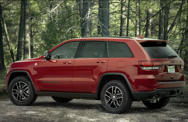 2021 Jeep Grand Cherokee red outside in forest facing left