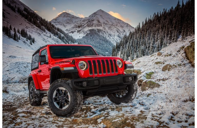 2021 Jeep Wrangler Rubicon red driving on snowy mountain trail